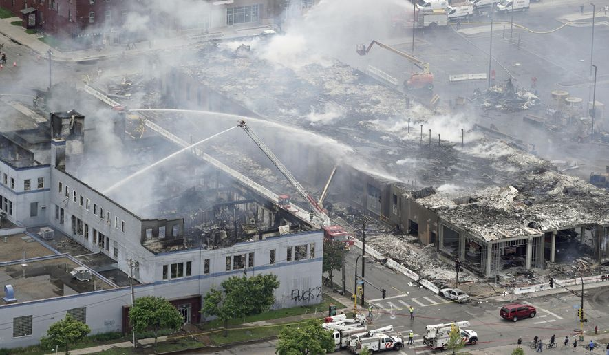 Firefighters work on an apartment building under construction, Thursday, May 28, 2020, tentatively known as Midtown Corner, left, after it was burned to the ground in Minneapolis, Minn. during protests. Minneapolis residents awoke Thursday to assess the damage after rioters ignited fires and looted stores all over the city, as peaceful protests turned increasingly violent in the aftermath the death of George Floyd during an arrest. (Brian Peterson/Star Tribune via AP)