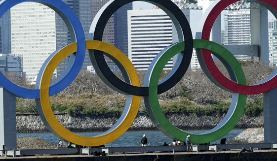 In this March 24, 2020, file photo, workers stand at the bottom of the Olympic rings at Tokyo's Odaiba district. Just two months after the unprecedented postponement. Chief Executive Toshiro Muto was asked Thursday, May 28, 2020 about progress rescheduling next year's Tokyo Olympics. (AP Photo/Eugene Hoshiko) ** FILE **