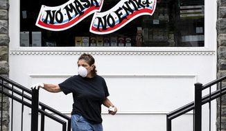 """A woman wearing a mask and gloves exits The Shop, a convenience store in downtown Milford, Pa. on Thursday, May 28, 2020. Pike County is moving to Governor Tom Wolf's """"yellow"""" phase of reopening on Friday. (Christopher Dolan/The Times-Tribune via AP)"""