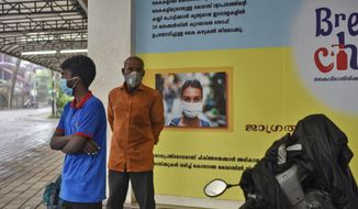 Indians wearing masks stand next to a signage that urges people to wash their hands and wear masks to protect against the COVID-19 pandemic in Kochi, Kerala state, India, Thursday, May 28, 2020. India sees no respite from the coronavirus caseload at a time when the two-month-old lockdown across the country is set to end on Sunday. (AP Photo/R S Iyer)