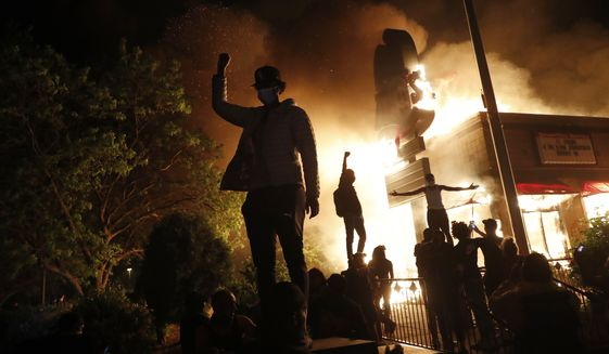 Protesters gather in front of a burning fast food restaurant Friday, May 29, 2020, in Minneapolis. Protests over the death of George Floyd, a black man who died in police custody Monday, broke out in Minneapolis for a third straight night. (AP Photo/John Minchillo)