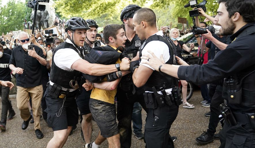 Uniformed U.S. Secret Service police detain a protester in Lafayette Park across from the White House as demonstrators protest the death of George Floyd, a black man who died in police custody in Minneapolis, Friday, May 29, 2020, in Washington. (AP Photo/Evan Vucci)