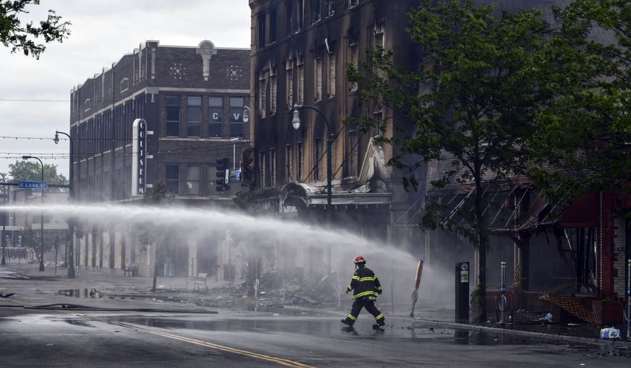 A firefighter walks past smoldering buildings after people rioting to protest the death of George Floyd lit fires on Thursday night near the intersection of Lake Street and Minnehaha Avenue Friday, May 29, 2020, in Minneapolis. Protests over the death of Floyd in Minneapolis police custody have spread to other areas across the United States. (Dave Schwarz/St. Cloud Times via AP)
