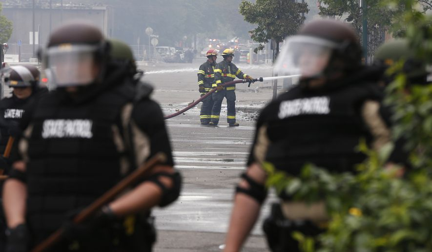 Minnesota state troopers provide protection as firefighters, center, battle a fire, Friday, May 29, 2020, in Minneapolis after another night of protests, fires and looting over the arrest of George Floyd who died in police custody Monday night in Minneapolis. Video shared online by a bystander showed a white officer kneeling on his neck during his arrest as he pleaded that he couldn't breathe. (AP Photo/Jim Mone)