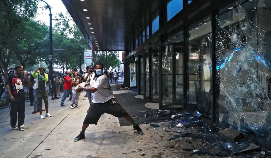 A protester smashes a window at the CNN center Friday, May 29, 2020, in Atlanta. They carried signs and chanted their messages of outrage over the death of George Floyd in Minneapolis. (Alyssa Pointer/Atlanta Journal-Constitution via AP)