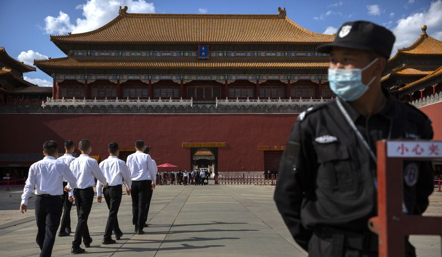 A security officer wearing a face mask to protect against the COVID-19 coronavirus stands guard as plainclothes personnel march in formation outside the entrance to the Forbidden City in Beijing, Wednesday, May 27, 2020. The Chinese People's Political Consultative Conference (CPPCC) concluded its session in Beijing on Wednesday, part of the annual meetings of China's two top legislative bodies. (AP Photo/Mark Schiefelbein)
