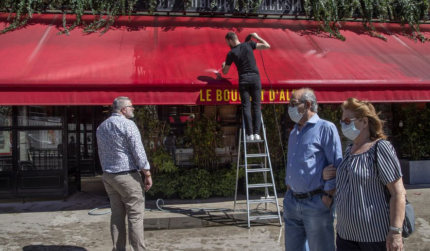 A man cleans the store of his restaurant as people wearing mask to help curb the spread of the coronavirus walks past in Paris, Friday, May 29, 2020, as France gradually lifts its Covid-19 lockdown. France is reopening next week its restaurants, bars and cafes starting next week as the country eases most restrictions amid the coronavirus crisis. (AP Photo/Michel Euler)