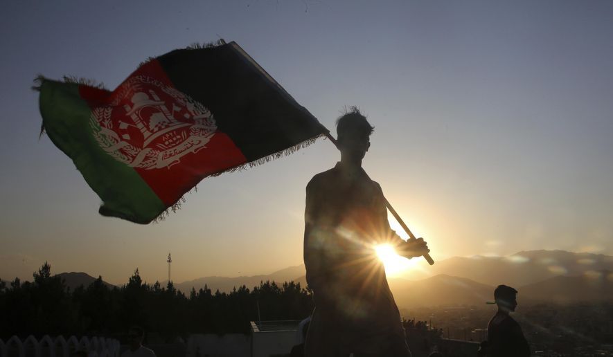 In this Aug. 19, 2019, photo, a man waves an Afghan national flag during Independence Day celebrations in Kabul, Afghanistan. Taliban fighters attacked an army checkpoint in eastern Afghanistan, killing 14 military personnel, the Defense Ministry said Friday, May 29, 2020. (AP Photo/Rafiq Maqbool) **FILE**