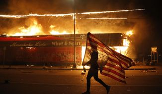 A protester carries the carries a U.S. flag upside, a sign of distress, next to a burning building Thursday, May 28, 2020, in Minneapolis. Protests over the death of George Floyd, a black man who died in police custody Monday, broke out in Minneapolis for a third straight night. (AP Photo/Julio Cortez)