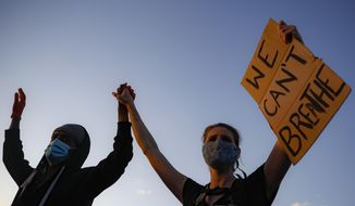 """Protestors demonstrate on University Avenue while holding a """"WE CAN'T BREATHE"""" sign and wearing protective masks, Thursday, May 28, 2020, in St. Paul, Minn. Protests over the death of George Floyd, a black man who died in police custody Monday, broke out in Minneapolis for a third straight night. (AP Photo/John Minchillo)"""