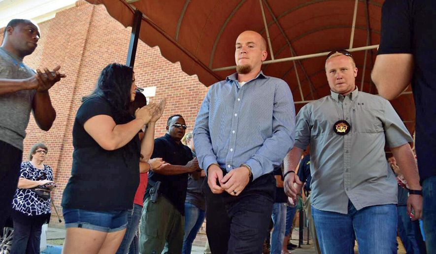 FILE - In this Sept. 9, 2016, file photo, former Columbus Police officer Canyon Boykin, center, is led from the Lowndes County Courthouse in handcuffs while people applaud in Columbus, Miss. The Mississippi attorney general said Thursday, May 28, 2020, that a manslaughter charge will be dropped against Boykin in the October 2015 shooting death of an African American man because her office reviewed the case and concluded the officer acted in self-defense. (Luisa Porter/The Commercial Dispatch via AP, File)