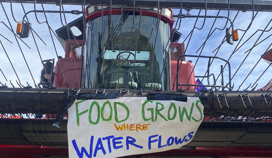 A sign is shown on the front of farm equipment near Merrill, Ore., Friday, May 29, 2020. Farmers upset about water issues planned a convoy in southwest Oregon. (Holly Dillemuth/Herald and News via AP)