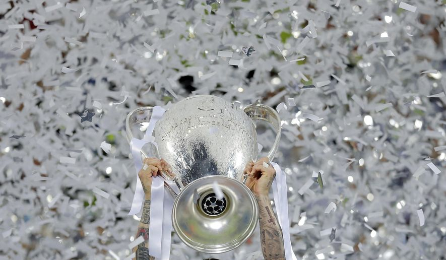 FILE - In this Saturday, May 28, 2016 file photo Real Madrid's Sergio Ramos celebrates with the trophy after the Champions League final soccer match between Real Madrid and Atletico Madrid at the San Siro stadium in Milan, Italy. In the absence of the Champions League final on Saturday, The Associated Press will take a look back at some of the greatest teams, players and matches in the history of the tournament. The AP will pick a topic for every letter of the alphabet to remember the greats of the game and the greatest games, going back to when the competition was called the European Cup and through its transformation into the Champions League. (AP Photo/Manu Fernandez, File)