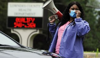 """In this May 27, 2020, photo, health care worker Tonya Wilkes adjusts her mask while working at a Lowndes County coronavirus testing site in Hayneville, Ala. Experts say Lowndes County and nearby poor, mostly black counties in rural Alabama are now facing a """"perfect storm"""" as infections tick up: a lack of access to medical care combined with poverty and the attendant health problems that can worsen the outcomes for those who become sick. (AP Photo/Jay Reeves)"""