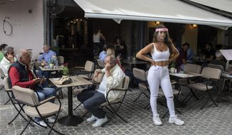 A cafe-restaurant staff stands outside as people drink coffee in Monastiraki district of Athens, on Monday, May 25, 2020.  Greece restarted regular ferry services to its islands Monday, and cafes and restaurants were also back open for business as the country accelerated efforts to salvage its tourism season. (AP Photo/Petros Giannakouris)