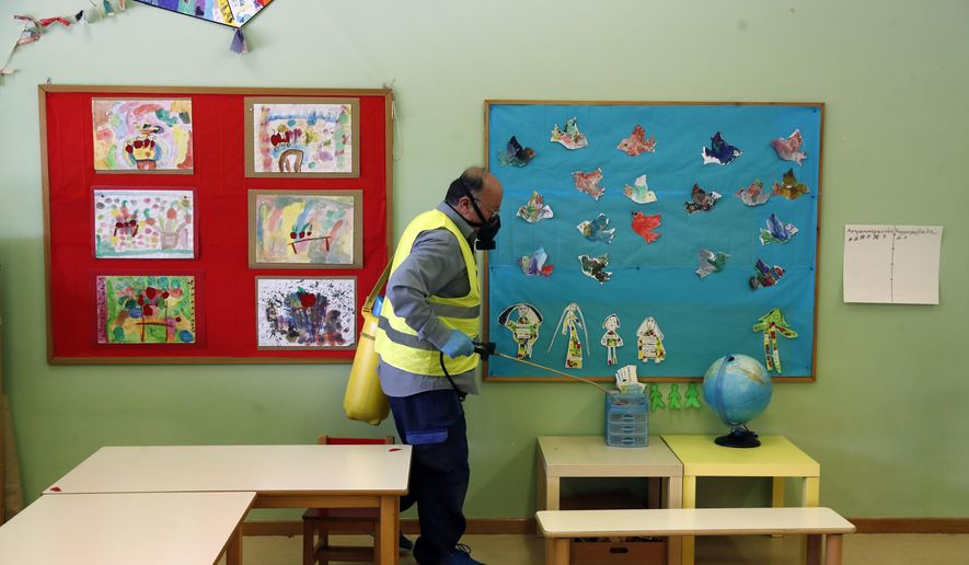 A worker wearing a protective mask sprays disinfectant inside a classroom of a kindergarten in the suburb of Halandri, northern Athens, Friday, May 29, 2020. Greece will reopen preschools, kindergartens and primary schools on Monday in the latest round of easing coronavirus pandemic restrictions imposed in late March. Classes will have no more than 15 children while the academic year will end on Friday, June 26. (AP Photo/Thanassis Stavrakis)