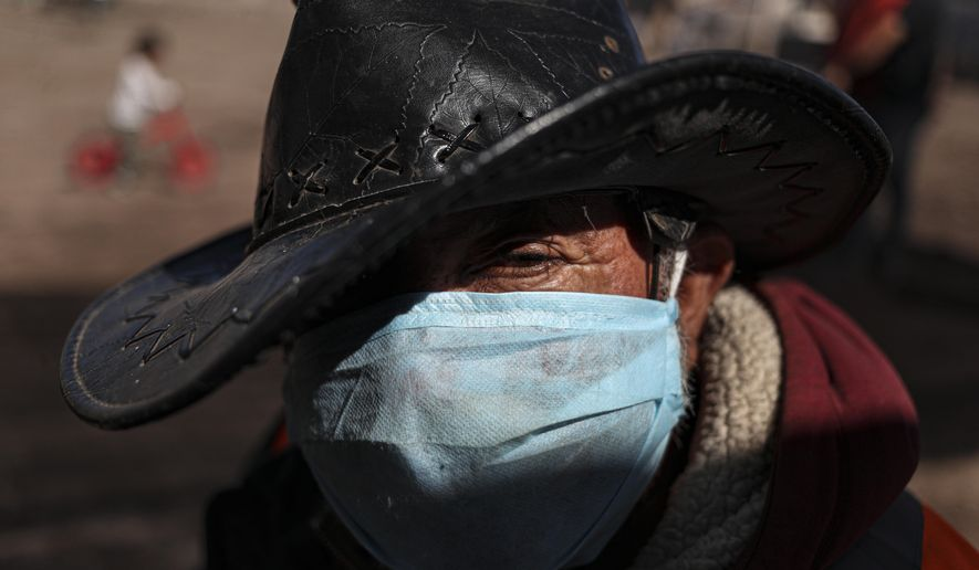 Hernaldo Gutierrez, wearing a protective face mask, waits in line to receive free fruits and vegetables from produce vendors who are donating their time and products to those facing hardship because of lost income due to the new coronavirus pandemic, in Quillicura, on the outskirts of Santiago, Chile, Wednesday, April 29, 2020. (AP Photo/Esteban Felix)