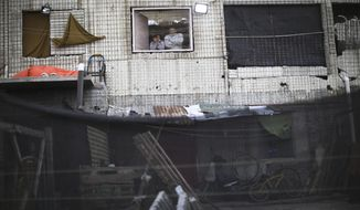 Residents look out their window in the Villa Azul neighborhood, quarantined by authorities after 50 some people tested positive for the new coronavirus, on the outskirts of Buenos Aires, Argentina, Monday, May 25, 2020. The virus initially brought to the region largely by wealthy citizens or visitors coming from Europe and the United States is now increasingly concentrated in poorer neighborhoods where residents have few means of protecting themselves. (AP Photo/Natacha Pisarenko)