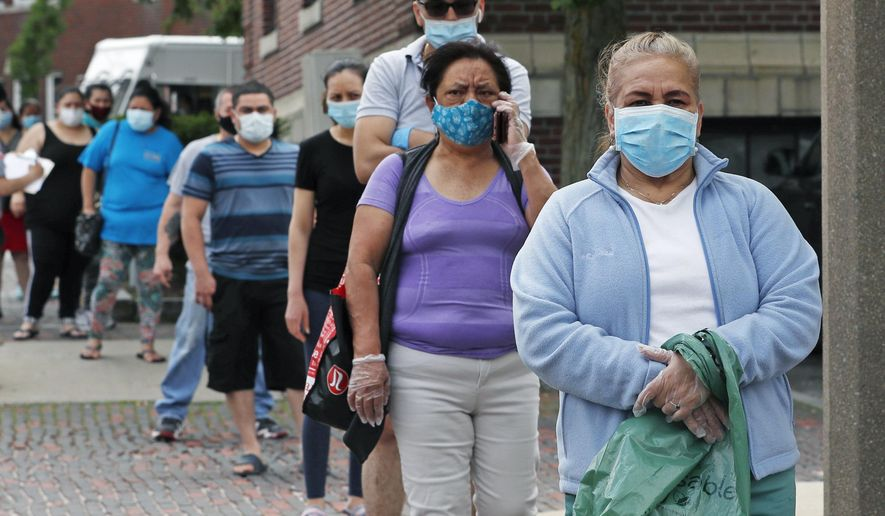 Residents wearing protective masks, due to the coronavirus outbreak, wait in line for boxes of donated food for those in need in Chelsea, Mass., Friday, May 29, 2020. (AP Photo/Charles Krupa)