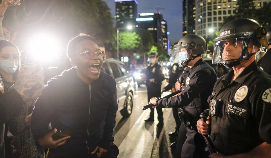 A protester yells at police while protesting the Monday death of George Floyd, a handcuffed black man in police custody in Minneapolis, in downtown Los Angeles, Friday, May 29, 2020. (AP Photo/Ringo H.W. Chiu)