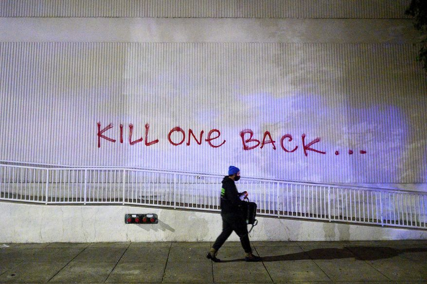 A demonstrator passes graffiti in Oakland, Calif., on Friday, May 29, 2020, while protesting the Monday death of George Floyd, a handcuffed black man in police custody in Minneapolis. A federal protective services officer was fatally shot Friday night, the FBI announced Saturday morning. (AP Photo/Noah Berger)