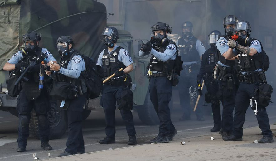 Police fire tear gas and less-lethal rounds at protesters during a demonstration at the intersection of East Lake Street and Hiawatha Avenue, Friday, May 29, 2020, in St. Paul, Minn. Protests continued following the death of George Floyd, who died after being restrained by Minneapolis police officers on Memorial Day. (AP Photo/John Minchillo)