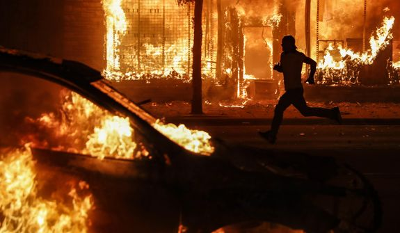 A protester runs past burning cars and buildings on Chicago Avenue, Saturday, May 30, 2020, in St. Paul, Minn. Protests continued following the death of George Floyd, who died after being restrained by Minneapolis police officers on Memorial Day. (AP Photo/John Minchillo)