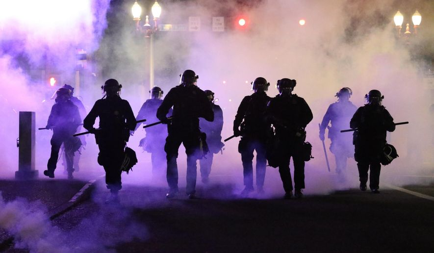 Police officers walk enveloped by teargas in Portland, Friday, March 29, 2020.  Afterhours of largely peaceful demonstrations,violence escalated late Friday in downtown Portland, as hundreds of people gathered toprotest the Minneapolis police killingof a black man, George Floyd . (Dave Killen/The Oregonian via AP)