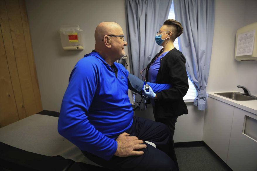 In this March 19, 2020 photo, Henry Stokloas has his blood pressure check during a routine visit to Dr. William Funk's primary care practice in Newark, Del., by nurse Sharon Cormier, who wears a protective mask at all times while treating patients. As the coronavirus continues to alter almost every aspect of life in Delaware, health care is no exception. Hospitals have reported significant financial losses. Practitioners are using telemedicine more than ever. And fewer patients are seeking health care. (Jennifer Corbett/The News Journal via AP)
