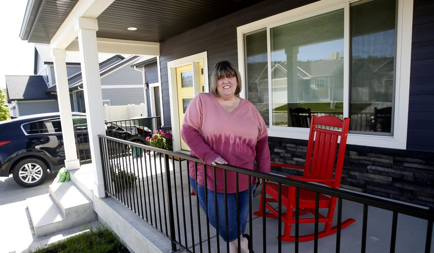 In this May 22, 2020, photo, Melisia Muscat stands on the front porch of her new home in Billings, Mont., that she and her husband bought sight-unseen before moving here from the Seattle area. Muscat had been thinking of moving to Billings for about a year, but the coronavirus pandemic sealed the deal. It helped that in February she got a good offer on her home, a condo in a highly sought-after building in the lush seaside city of Anacortes, Wash., north of Seattle. (Casey Page/The Billings Gazette via AP)