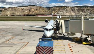 In this May 25, 2020 photo, an American Airlines jet is seen parked on the tarmac at Colorado's Eagle County Airport in Gypsum, Colo., before departing on a 29-mile flight to Aspen, the shortest commercial jet flight in the country. The U.S. Department of Transportation is allowing American to cancel the route, which it was forced to fly to meet federal rules in a $58 billion coronavirus stimulus package for airlines (Jason Blevins/The Colorado Sun via AP).