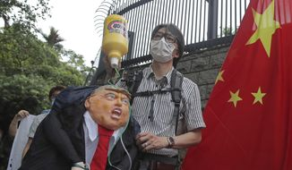 Pro-China supporters hold the effigy of U.S. President Donald Trump and Chinese national flag outside the U.S. Consulate during a protest in Hong Kong, Saturday, May 30, 2020. President Donald Trump has announced a series of measures aimed at China as a rift between the two countries grows. He said Friday that he would withdraw funding from the World Health Organization, end Hong Kong's special trade status and suspend visas of Chinese graduate students suspected of conducting research on behalf of their government. (AP Photo/Kin Cheung) **FILE**