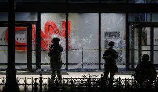 Members of the Georgia National Guard stand in front of shattered glass at the CNN Center in the aftermath of a demonstration against police violence on Saturday, May 30, 2020, in Atlanta. (AP Photo/Brynn Anderson)