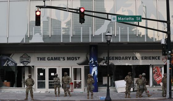 The Georgia National Guard lines up in front of the of the College Football Hall of Fame in the aftermath of a demonstration against police violence on Saturday, May 30, 2020, in Atlanta. (AP Photo/Brynn Anderson) ** FILE **
