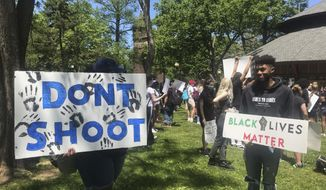 A pair of demonstrators hold signs at Bushnell Park in Hartford, Conn., Saturday, May 30. 2020, to protest the death of George Floyd, a black man who was killed in police custody in Minneapolis on May 25. (Daniela Altimari//Hartford Courant via AP)