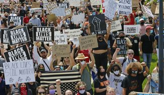 Protesters march near the Salt Lake City Police Department to protest the death of George Floyd during a rally Saturday, May 30, 2020, in Salt Lake City. Protests across the country have escalated over the death of George Floyd who died after being restrained by Minneapolis police officers on Memorial Day.(AP Photo/Rick Bowmer)