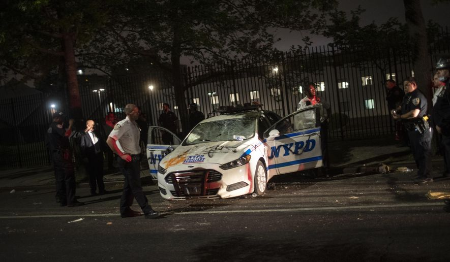 Policemen surround a NYPD vehicle after it was vandalized by protestors over the death of George Floyd, a black man who was in police custody in Minneapolis, on Saturday, May 30, 2020, in the Brooklyn borough of New York. Floyd died after being restrained by Minneapolis police officers on Memorial Day. (AP Photo/Wong Maye-E)