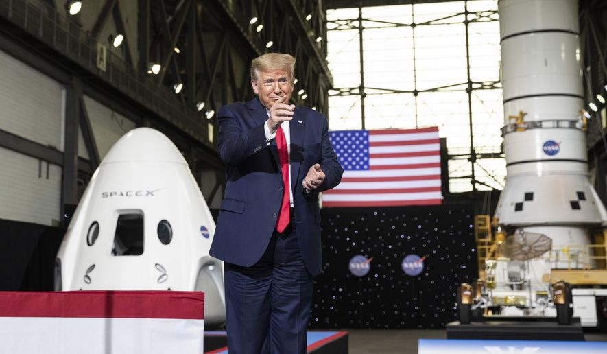 President Donald Trump points to Elon Musk as he arrives to speak after viewing the SpaceX flight to the International Space Station, at Kennedy Space Center, Saturday, May 30, 2020, in Cape Canaveral, Fla. (AP Photo/Alex Brandon)