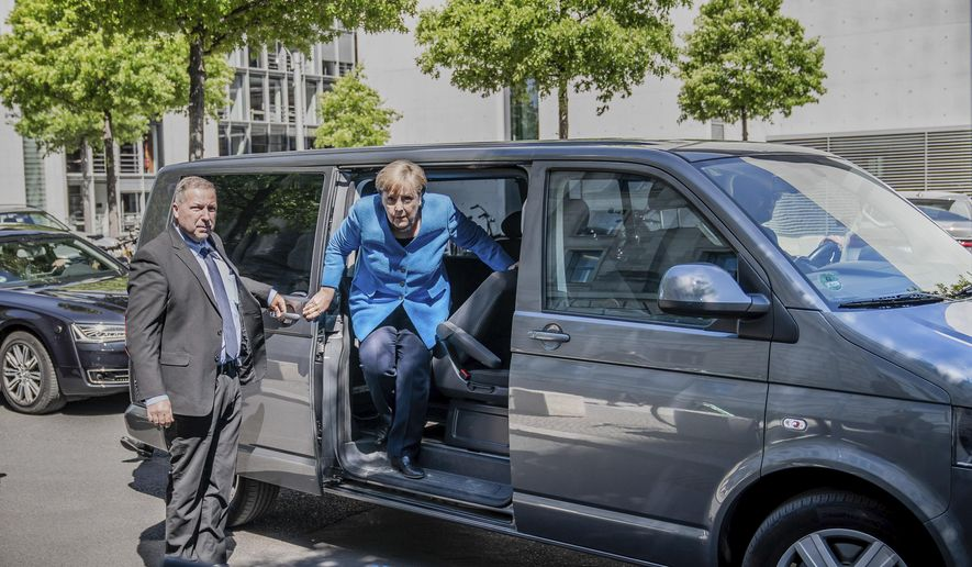 Chancellor Angela Merkel steps out of a minibus as she arrives for a parliament session at the Reichstag building in Berlin, Germany, Friday, May 29, 2020. Because of the coronavirus crisis the Merkel is chauffeured in a minibus in order to keep the distance rules. (Michael Kappeler/dpa via AP)