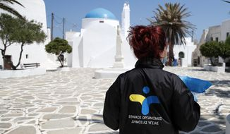 In this Monday, May 25, 2020 photo, a doctor of the National Health Organization (EODY) carries the tests for coronavirus taken on local residents on the Aegean Sea island of Sikinos, Greece. Using dinghies, a GPS, and a portable refrigerator, state doctors have launched a COVID-19 testing drive on islands in the Aegean Sea ahead of the holiday season, authorities in charge of the program said. The first round of testing was completed after trips to the islands of Milos, Kimolos, Folegandros, and Sikinos. (AP Photo/Thanassis Stavrakis)