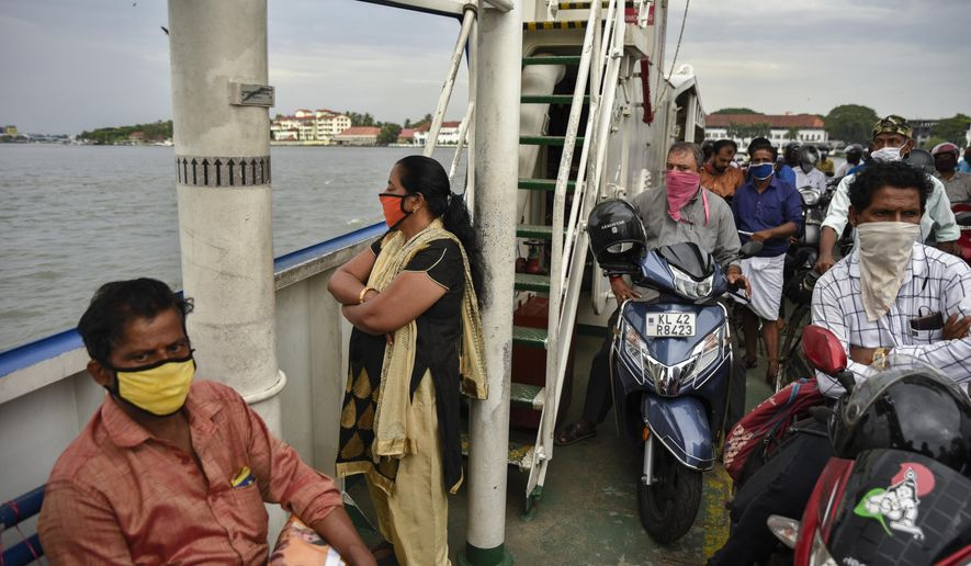 Indians wearing masks travel in a ferry during the coronavirus pandemic in Kochi, Kerala state, India, Friday, May 29, 2020. Prime Minister Narendra Modi's government is preparing a new set of guidelines to be issued this weekend, possibly extending the lockdown in worst-hit areas while promoting economic activity elsewhere, with unemployment surging to 25%. (AP Photo/R S Iyer)