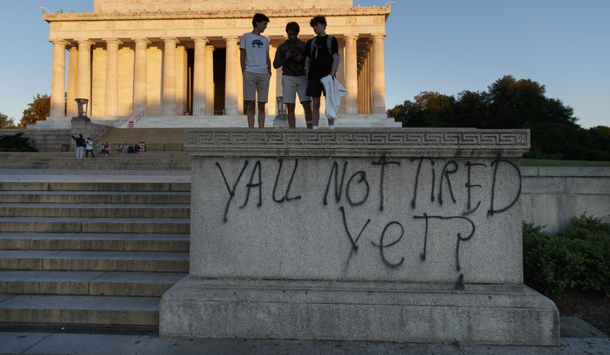 "Spray paint that reads ""Yall Not Tired Yet?"" is seen on the base fo the Lincoln Memorial on the National Mall in Washington, early Sunday, May 31, 2020, the morning after protests over the death of George Floyd. Floyd died after being restrained by Minneapolis police officers on Memorial Day. (AP Photo/Carolyn Kaster)"
