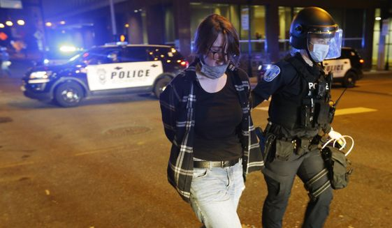 A protester is led away by police after being arrested during a third night of unrest Sunday May 31, 2020, in Richmond, Va. Gov. Ralph Northam issued a curfew for this evening. (AP Photo/Steve Helber)