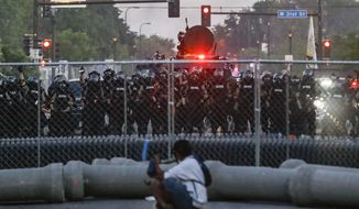 Police in riot gear advance on protesters near the 5th Police Precinct, Saturday, May 30, 2020, in Minneapolis. Protests continued following the death of George Floyd, who died after being restrained by Minneapolis police officers on Memorial Day. (AP Photo/John Minchillo)
