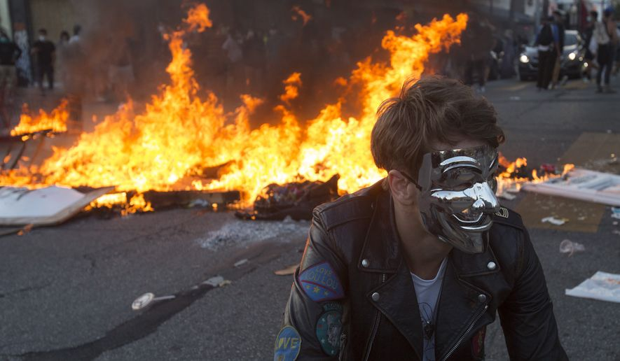 A protester wearing mask poses for photos in front of a fire during a protest over the death of George Floyd, a handcuffed black man in police custody in Minneapolis, in Los Angeles, Saturday, May 30, 2020. (AP Photo/Ringo H.W. Chiu)