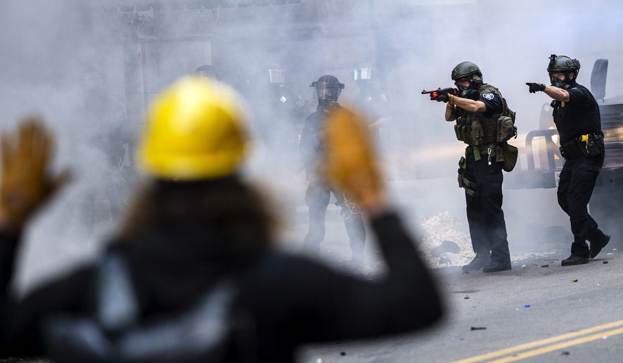 Police officers confront protesters during a  demonstration demanding justice for George Floyd, Saturday, May 30, 2020, on Sixth Street in downtown Pittsburgh. Protests continue across the country over the death of Floyd, a black man who died after being restrained by Minneapolis police officers on May 25. (Michael M. Santiago/Post-Gazette via AP)