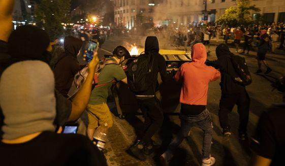 Demonstrators push a burning dumpster toward police during a protest over the death of George Floyd, Saturday, May 30, 2020, near the White House in Washington. Floyd died after being restrained by Minneapolis police officers. '(AP Photo/Evan Vucci)
