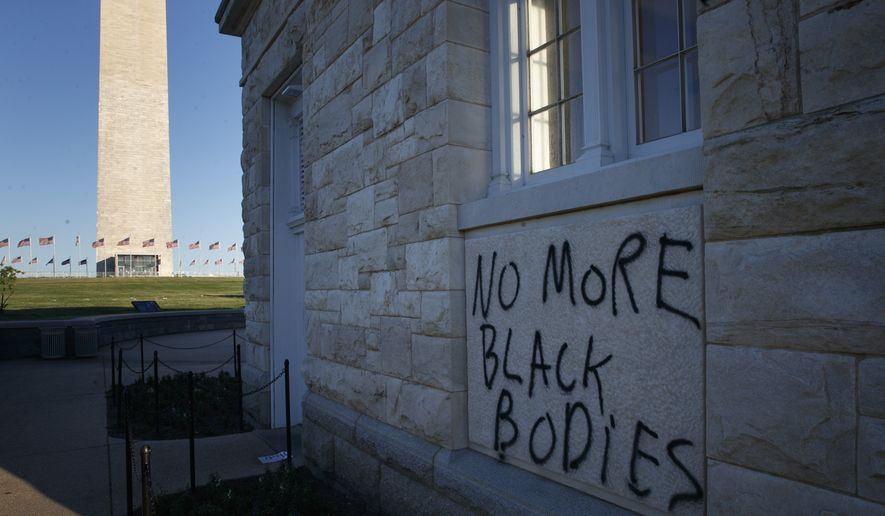 """Spray paint that reads """"No More Black Bodies"""" is painted near the Washington Monument on the National Mall in Washington, Sunday, May 31, 2020, after protests over the death of George Floyd. Floyd died after being restrained by Minneapolis police officers on Memorial Day. (AP Photo/Carolyn Kaster)"""