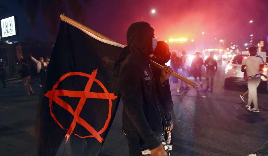 A man carries a flag depicting the anarchist symbol during a public disturbance on Melrose Avenue, Saturday, May 30, 2020, in Los Angeles. Protests were held in U.S. cities over the death of George Floyd, a black man who died after being restrained by Minneapolis police officers on May 25. (AP Photo/Chris Pizzello)