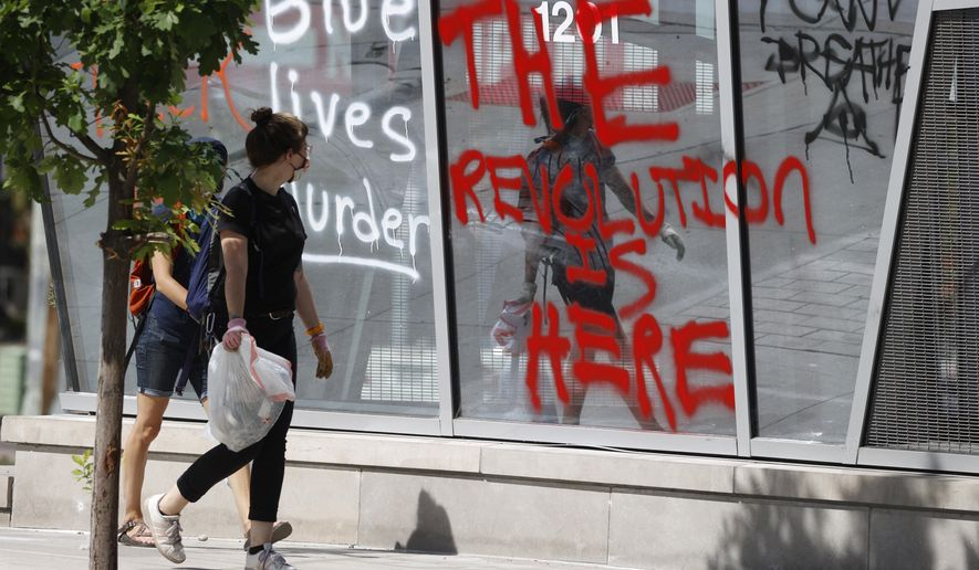Citizens who were cleaning up pass by graffiti scrawled on the windows of the ART Hotel during rioting after a protest outside the nearby State Capitol over the death of George Floyd, a handcuffed black man in police custody in Minneapolis, Sunday, May 31, 2020, in Denver. (AP Photo/David Zalubowski)